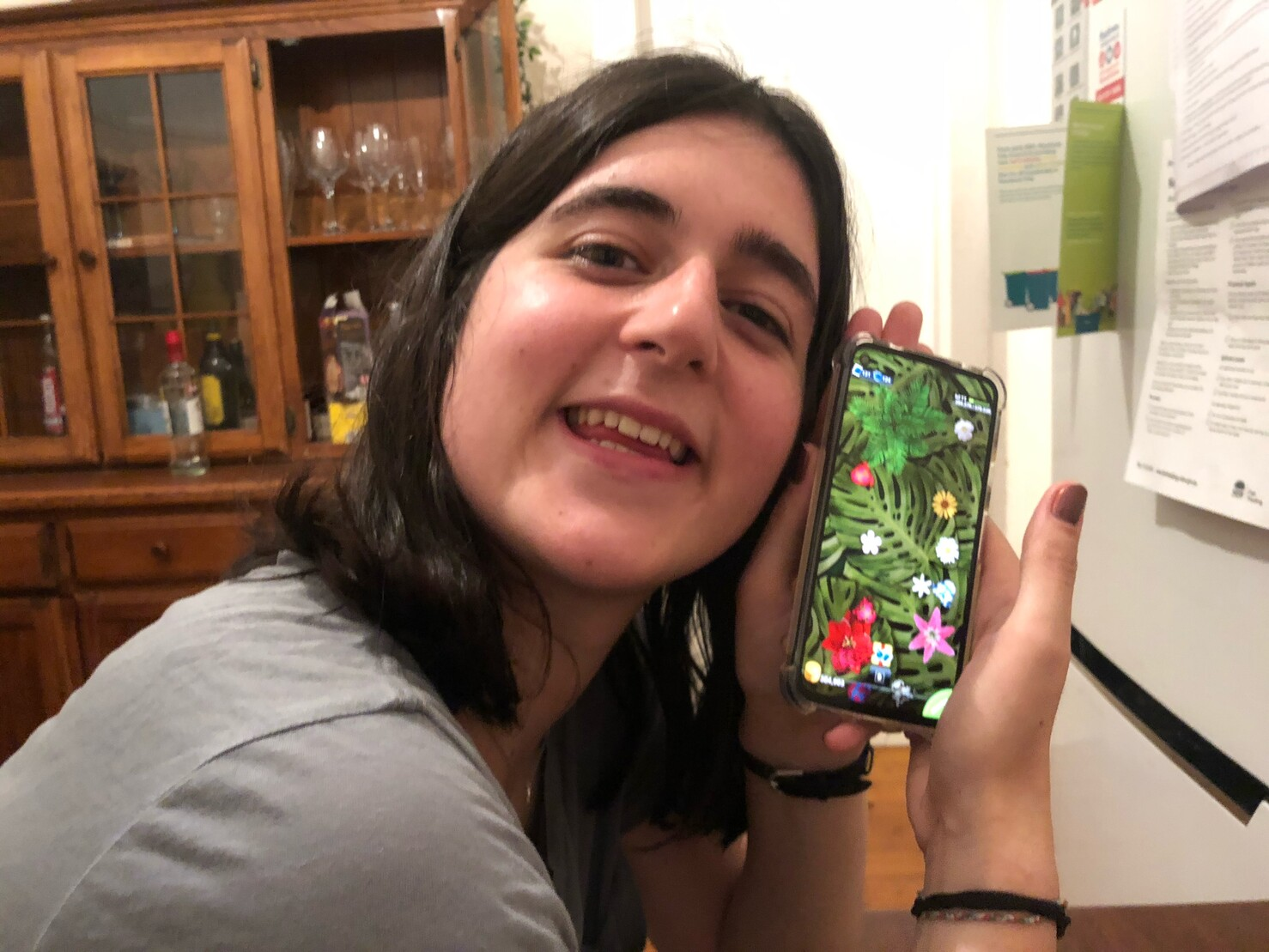 Photo of my partner, a young Caucasian woman with wavy shoulder-length brown hair holding her phone up with the Pocket Frogs game, and grinning very cutely.